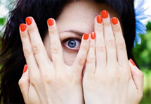 девушка смотрит через пальцы