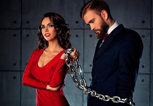 женщина держит мужчину на цепи