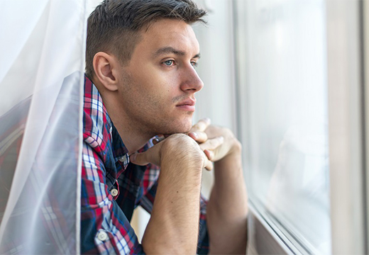 парень смотрит в окно