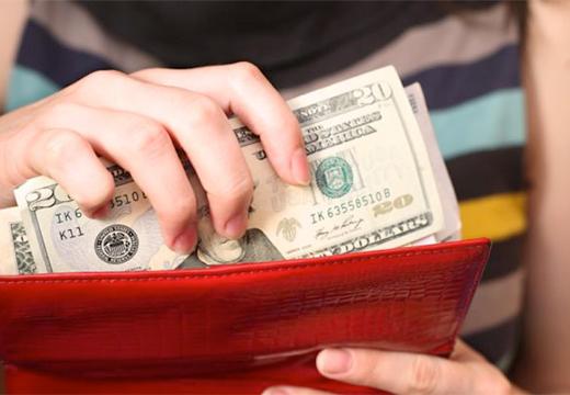 кладет доллары в кошелек