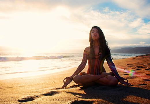 медитирует на пляже