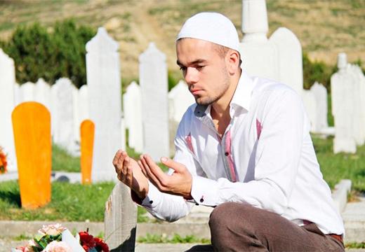 парень молится у могилы