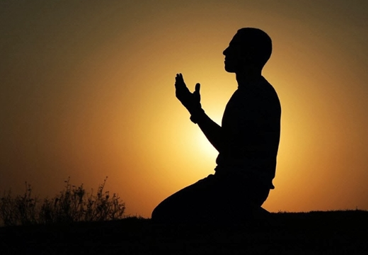 мужчина молится на закате
