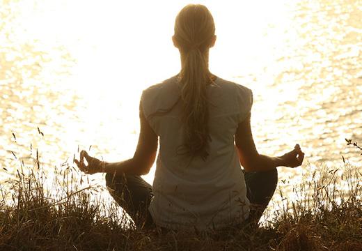 женщина медитирует на берегу