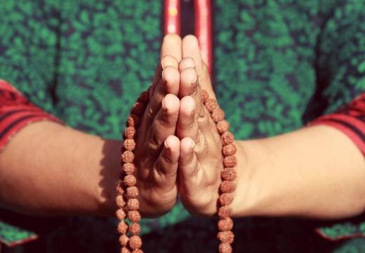 молится с четками