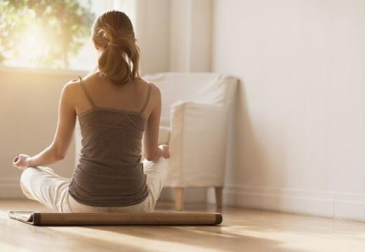 женщина медитирует у окна