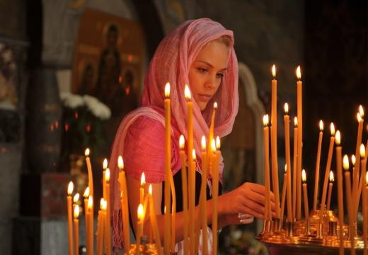 девушка ставит свечку