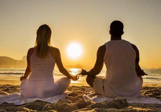 пара медитирует на пляже