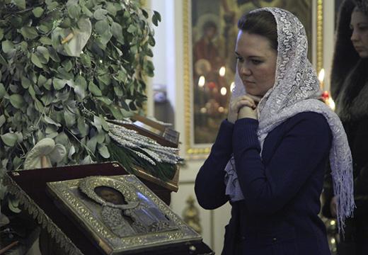 Девушка молится в церкви