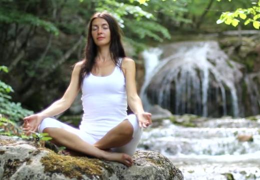 девушка медитирует у водопада