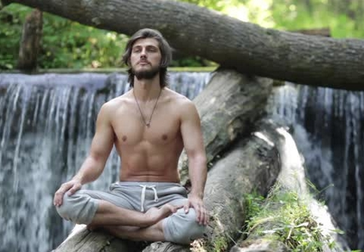 мужчина в позе лотоса у водопада