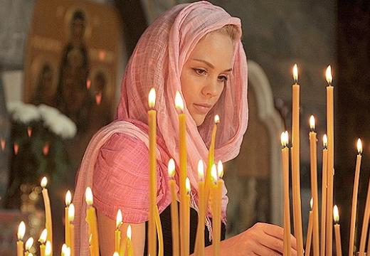 Девушка ставит свечу