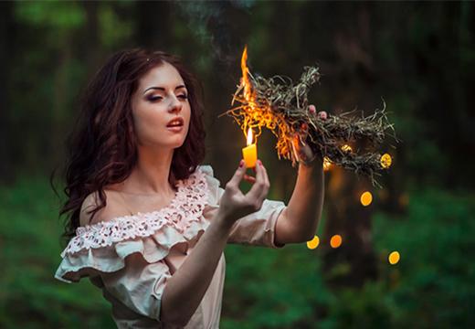 Девушка поджигает травы
