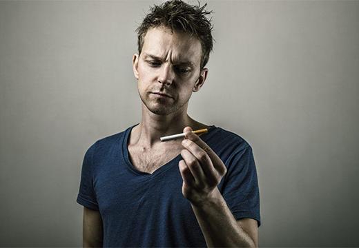 мужчина смотрит на сигарету
