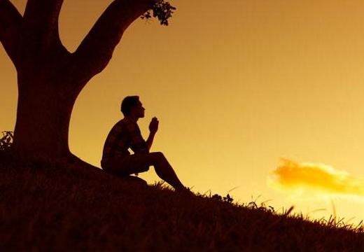 мужчина молится под деревом