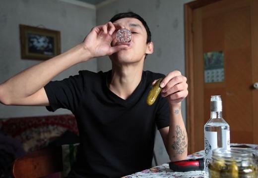 молодой парень пьет водку